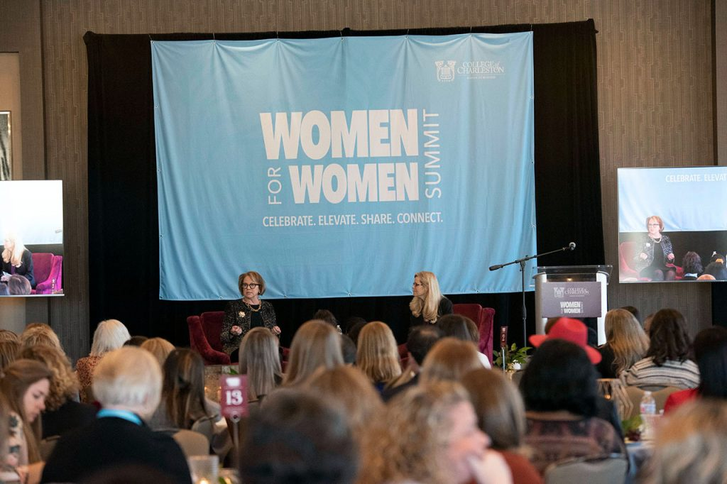 Wide shot of speakers on stage and attendees in audience at the Women for Women Summit presented by the College of Charleston School of Business